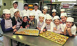 De leerlingen hopen honderden hartvormige koekjes te verkopen. Louis Verbraeken