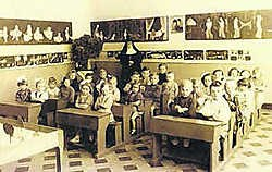 Een klas van de school met de oude zitbanken, een zandbak op de voorgrond en een zuster die surveilleert. jdv