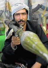 Een ex-Talibanstrijder overhandigt zijn wapen tijdens een ceremonie in Herat (Afganistan). pn