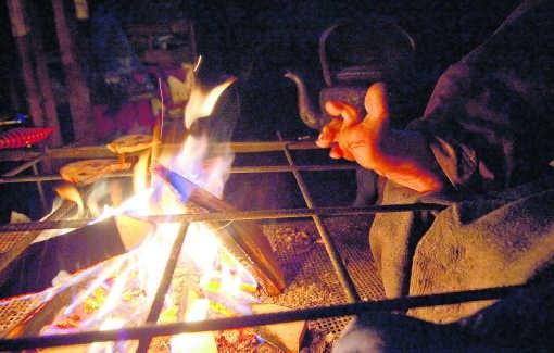 Een tiental bezetters verzamelt 's avonds rond het kampvuur om te keuvelen en zich te verwarmen.