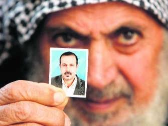 De vader van Mahmoud al-Mabhouh toont een foto van zijn vermoorde zoon. reuters