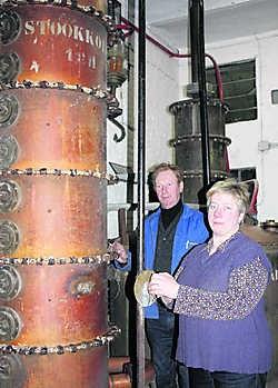 Ludo en Dominique Lampaert, die vandaag de stokerij leiden, poseren bij de originele stookkolom. dpw