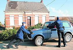 De politie duwt een wagen weg voor een van de veroordeelde hoeves. ena
