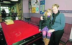 Linda Matthijs en haar kleindochtertje Jade bij de biljart. Die werd beschadigd, maar is al hersteld. Michel Moens