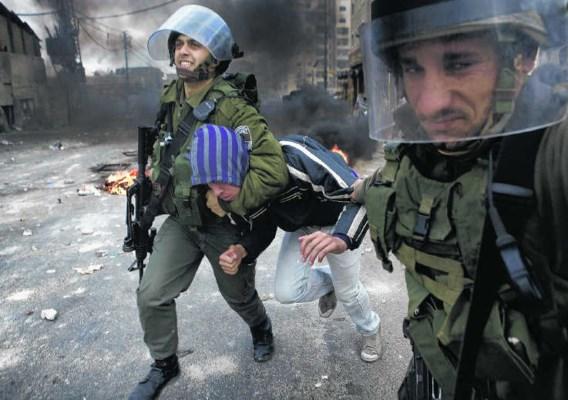 Israëlische oproerpolitie pakt een jonge Palestijn op tijdens rellen in het vluchtelingenkamp Shufat in Oost-Jeruzalem. Marco Longari/afp
