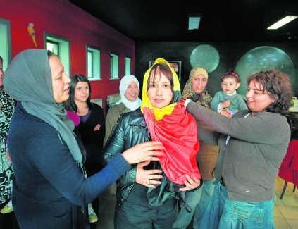 Voor de foto draperen de vrouwen van het naaiatelier in Genk de Belgische vlag graag rond het hoofd. Eric de Mildt