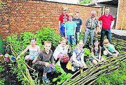 De kinderen van het vierde leerjaar samen met tuinvrijwilliger Aloïs Van De Velde, juf Kathleen De Cooman en meester Johan Van Der Meulen. Hendrik De Rycke