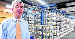 Gedelegeerd bestuurder van Helioscreen Luc Janvier aan de scheer- molen, waar 500 bobijnen met glasvezeldraden bevestigd zijn. lvs