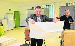 Burgemeester Willy De Waele van Lennik opent zijn stembrief maar geeft hem meteen terug aan de voorzitter van het stembureau. yds