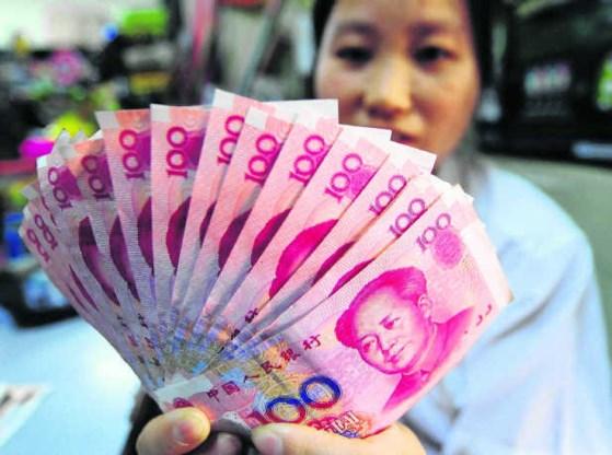 Een Chinese kruidenier toont zijn briefjes van 100 yuan. Worden Chinese exportproducten straks duurder?afp