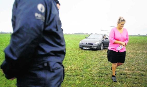 Een vrouw van de Franse zigeunergroep verlaat het terrein in Wingene terwijl de arm der wet toekijkt. 'Het racisme is overal', vindt hun internationale leider Mario Holderbaum.Jorge Dirkx/belga