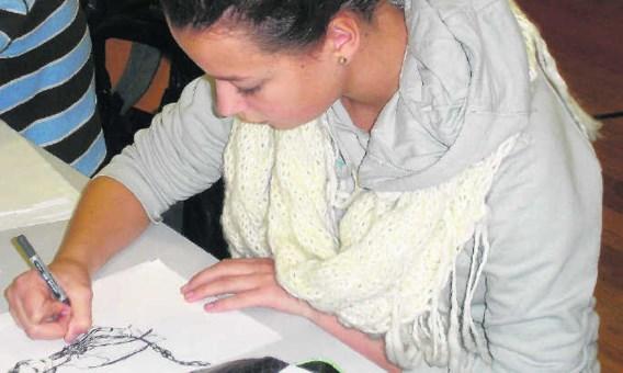 Manon Van Den Eeden tekent ijverig verder aan haar kunstwerk dat een jaar lang te zien zal zijn in de wandelboulevard van het MAS. mtv