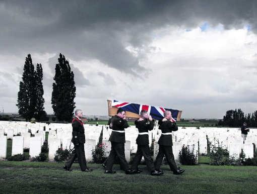Militairen dragen de kist met stoffelijke resten van een Britse soldaat naar zijn laatste rustplaats op de militaire begraafplaats Tyne Cot in Zonnebeke.Joost van den Broek