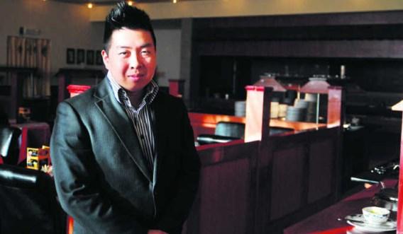 Uitbater Waiki Wang staat in zijn restaurant. Een deel van zijn personeelsleden heeft hij moeten ontslaan. phh