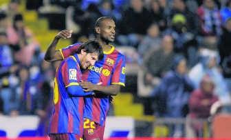 De kleine ster Lionel Messi viert in de armen van de lange Eric Abidal. afp