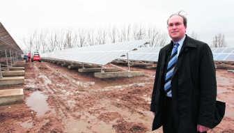 Roeland Vanhille van Eternit bij de zonnepanelen op het vroegere asbeststort. evr