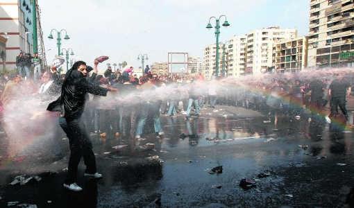 In Caïro probeert een betoger stand te houden tegen de waterkanonnen van de politie.rtr