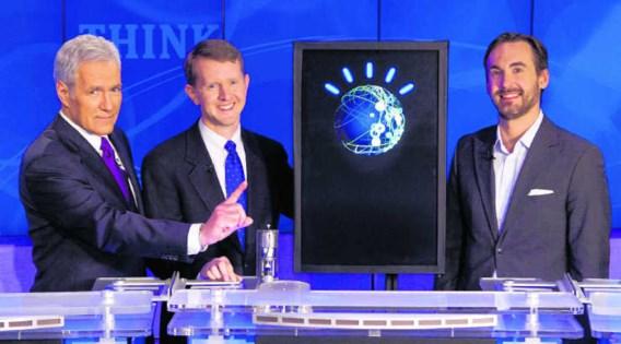 De presentator en de kandidaten van 'Jeopardy' rond het scherm van de moeilijk te kloppen quizcomputer Watson.ap