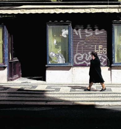 Een vrouw loopt voorbij een gesloten winkel de benedenstad van Lissabon.ap