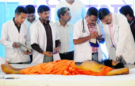 Een arts controleert de gezondheidstoestand van Baba Ramdev; zijn hongerstaking ging vrijdag haar zevende dag in. Gurinder Osan/ap