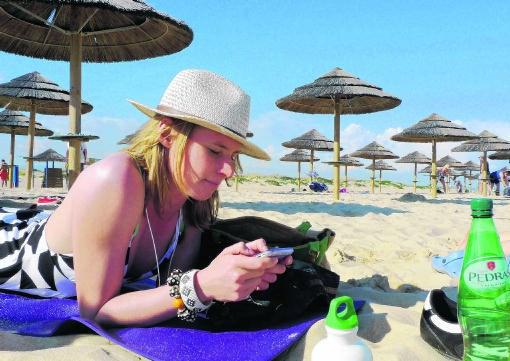 Op een Portugees strand lekker lui met je gsm internetten, is vandaag erg duur.Inge van Mill/Hollandse Hoogte