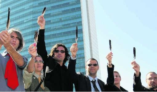 Een groep artiesten protesteert in Sarajevo tegen de politieke stilstand door met kraaienveren te zwaaien.ap