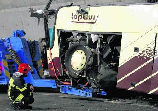 Een brandweerman inspecteert het wrak van de bus dat wordt getakeld.Denis Balibouse/reuters