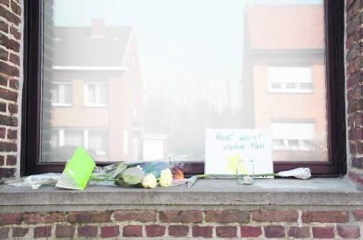 Voorbijgangers legden bloemen, kaarten en kaarsen bij het huis waar de baby werd gedood. belga