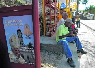 Een ambachtsman in El Cobre werkt aan een religieus beeldje. Naast hem hangt een affiche die het pausbezoek aankondigt.afp