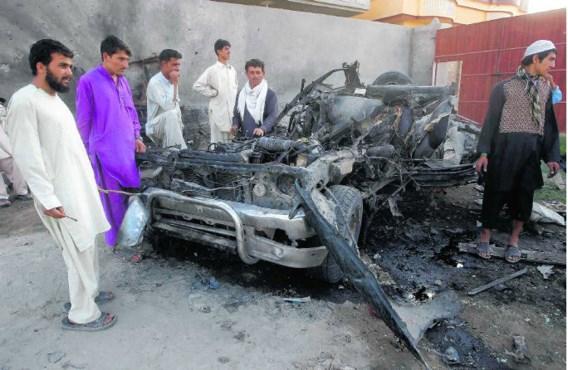 Inwoners van Jalalabad troepen samen rond het wrak van bomauto.Parwiz/reuters