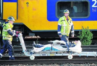 Een gewonde wordt weggevoerd na de treinbotsing. novum