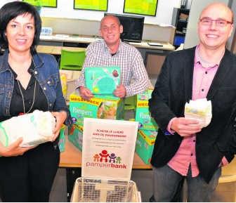 Schepen Vanessa Vens (l), gemeenteraadslid Niko Geldhof (r) en Patrick Blondé van het Opvoedingshuis (achteraan) stellen de Pamperbank voor.dji