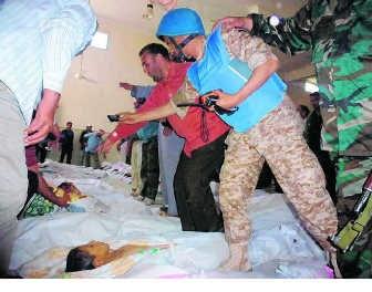 Een lid van de VN-waarnemingsmissie neemt foto's van slachtoffers in een moskee in Houla. reuters