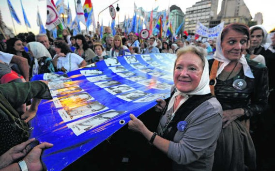 De grootmoeders van de Plaza de Mayo dragen een grote vlag met de portretten van de vermiste kinderen.