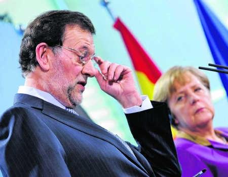 Angela Merkel werpt Mariano Rajoy een strenge blik toe.