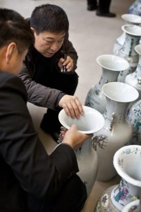De mogelijke Chinese kopers inspecteren kritisch de vazen.