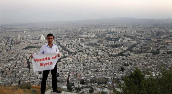 Aanhangers van het regime hebben een campagne georganiseerd om een 'menselijk schild' te vormen tegen een mogelijke Amerikaanse aanval. 'Handen af van Syrië', zegt deze activist op de Qasioun-berg, die uitkijkt over Damascus.