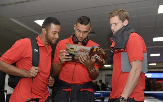 Jan Vertonghen (r.) kijkt met Tottenham-ploegmaats Moussa Dembele (l.) en Nacer Chadli een tijdschrift in bij de aankomst op de luchthaven van Glasgow.
