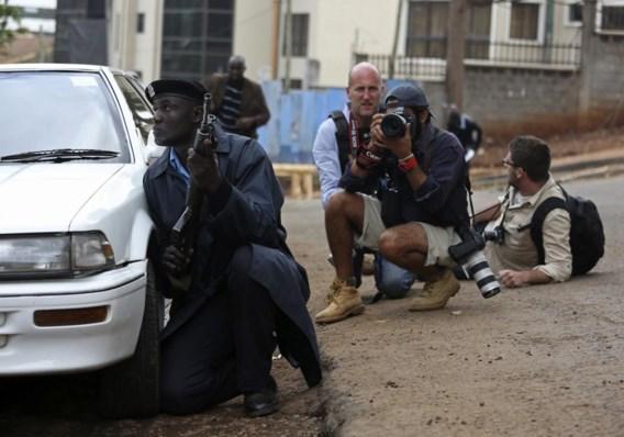 Een politieman en fotografen zoeken dekking nadat er geweerschoten te horen waren in het Westgate-shoppingcentrum.