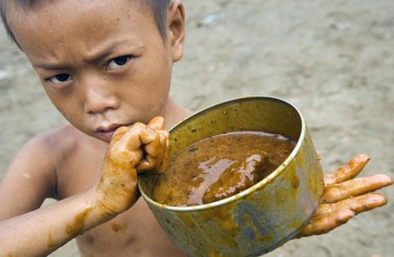 Dit jongetje uit Myanmar toont het blik waarmee hij heel de dag melasse moet ophalen.