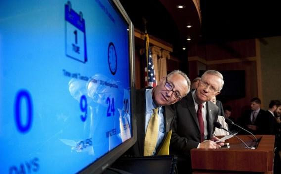 Harry Reid, de leider van de Democratische meerderheid in de Senaat (r.), en de Democratische senator Chuck Schumer kijken hoeveel tijd er nog rest tot de 'shutdown'.