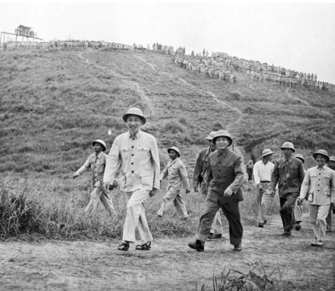 President Ho Chi Minh (links) en generaal Giap (tweede van links) bezoeken in 1957 een legereenheid in Vietnam.
