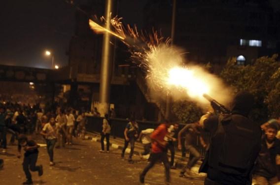 Een agent van de oproerpolitie vuurt traangas af naar betogers in een straat die leidt naar het Tahrirplein.