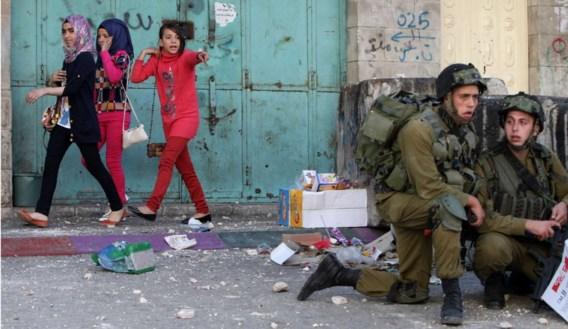 Palestijnse meisjes haasten zich weg terwijl Israëlische militairen dekking zoeken voor stenen gooiende Palestijnen nabij een controlepost in de stad Hebron, op de Westelijke Jordaanoever. Het kwam daar gisteren tot rellen toen het Israëlische leger jacht maakte op een Palestijnse militant die verdacht werd van betrokkenheid bij een bomaanslag op een bus in Tel Aviv, in november vorig jaar. Uiteindelijk werd de man, Mohammed Assi (28), doodgeschoten bij een vuurgevecht in de buurt van Bilin.