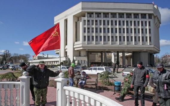 Een man zwaait met een Sovjetvlag voor het parlement in Simferopol.