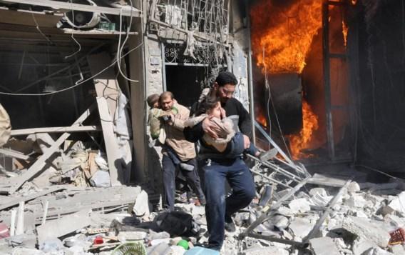 Twee mannen redden kinderen uit een brandend gebouw na een bombardement met 'barrel bombs'.