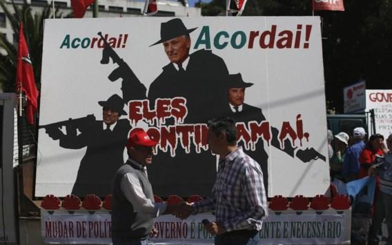 In een 1 mei-optocht in Lissabon voeren betogers een affiche mee waarop premier Passos Coelho (rechts), president Anibal Cavaco Silva (midden) and vicepremier Paulo Portas worden afgeschilderd als gangsters.
