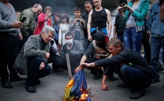 Pro-Russische betogers verbranden een Oekraïense vlag voor een districtgebouw in de Oost-Oekraïense stad Donetsk.