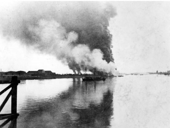 Brandende olietanks na de val van Antwerpen.