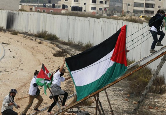 Een Palestijnse vlag wordt de scheidingsmuur over geleid nabij Ramallah.